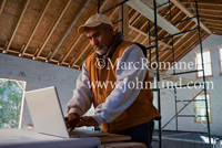 Hispanic man working on a laptop at a constructions site. Bare rafters visible in background.
